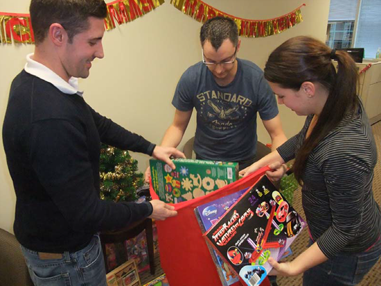 Office of the Procurement Ombudsman employees insert an immense bag full of toys to contribute to the Ottawa Toy Mountain toy drive.